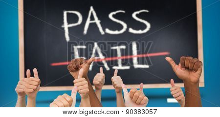 Hands giving thumbs up against pass and fail written on blackboard