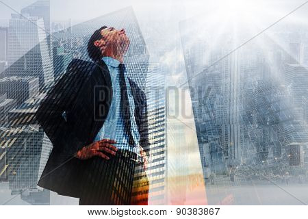 Cheerful businessman with hands on hips against low angle view of skyscrapers at sunset