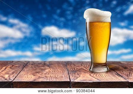 Beer in glass on wooden table against blue sky and clouds on natural background with bokeh