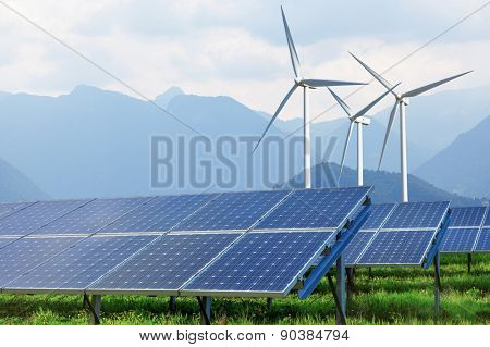 solar panels and wind turbines on summer landscape with mountains on background