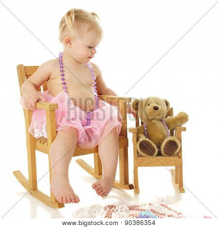 An adorable 2-year-old in a necklace. tutu and rocking chair.  She's rocking her toy bear in a miniature look-alike rocker.  On a white background.