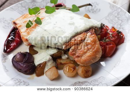 Grilled chicken steak in gorgonzola sauce served with roasted potato and vegetables on wooden table