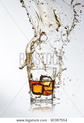 Whiskey ice drink with splash on gray background
