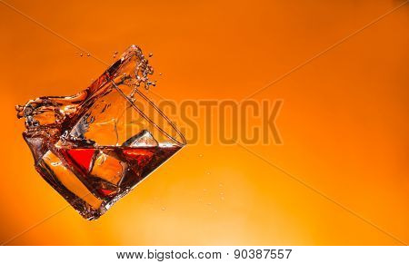 Whiskey ice drink with splash on orange background