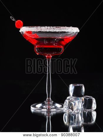 Martini drink served on glass table with black background and ice cubes