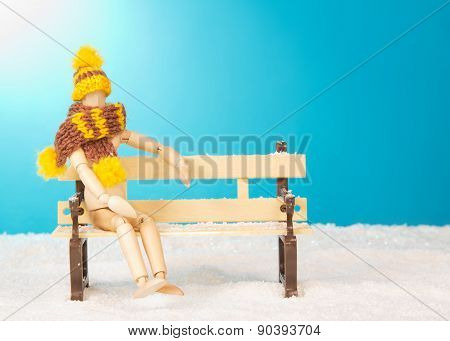 Wooden mannequin on bench