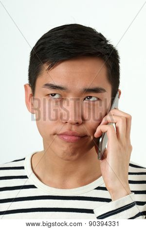 Frustrated young Asian man using a smartphone.