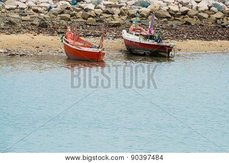 Small Fishing Boats Float On See Near Cement Breakwater