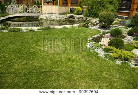 Arbor in garden with flowerbed, colorful plants and pond