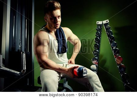 Strong Tired Bodybuilder Athlete With Protein Shaker And Towel