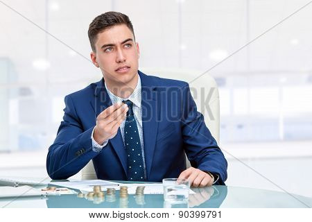 Businessman At Desk Holding Money With Worried Face Expression
