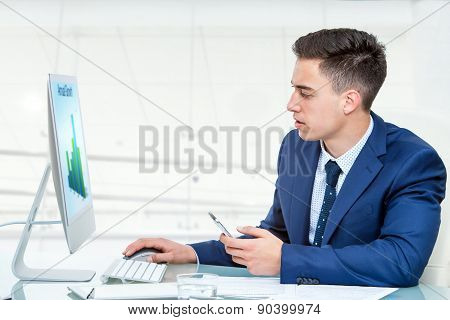 Businessman Synchronizing Smart Phone With Computer