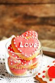 stock photo of glass heart  - Heart shaped cookies for valentines day in glass jar on color wooden background - JPG
