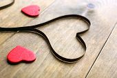 image of magnetic tape  - Magnetic tape in shape of heart on wooden background - JPG