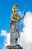 stock photo of goddess  - Statue and fountain of Pallas Athena Brunnen greek goddess of wisdom in golden helmet in front of Parliament building in Vienna Austria against the blue cloudy sky - JPG