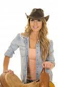 picture of cowgirls  - A cowgirl standing next to her saddle with a big smile on her lips - JPG