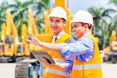 stock photo of mines  - Asian engineer controlling construction machinery of construction site or mining company - JPG
