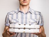 image of take out pizza  - Pizza delivery courier in shirt holding two boxes with pizza - JPG