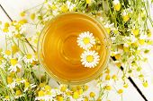 foto of chamomile  - cup of chamomile tea with chamomile flowers on white wooden planks - JPG
