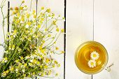 image of chamomile  - cup of chamomile tea with chamomile flowers on white wooden planks - JPG