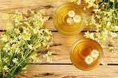 picture of chamomile  - cups of chamomile tea with chamomile flowers on wooden planks - JPG