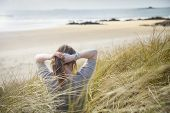 foto of tied hair  - A woman tying her hair up whilst sitting in the dunes on a beach - JPG