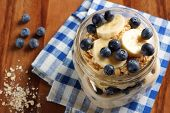 stock photo of masonic  - Blueberry and banana breakfast overnight oatmeal in a mason jar with checkered cloth on wood - JPG