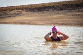 stock photo of swimming  - An active female is seen swimming across a dam while wearing a pink swimming cap - JPG