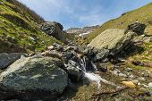 picture of mountain-range  - Little mountain streams from melting snow flowing in idyllic uncontaminated environment - JPG