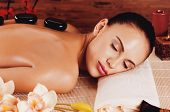 stock photo of stone-therapy  - Adult woman relaxing in spa salon with hot stones on back - JPG