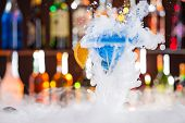 stock photo of vapor  - Cocktail with ice vapor on bar desk - JPG