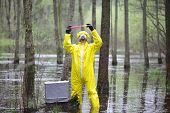 Постер, плакат: professional in protective coveralls with mini lab in contaminated environment