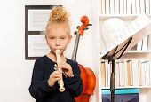 image of cello  - Blond curly girl plays flute standing near the cello in musical school - JPG