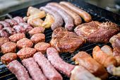 picture of grilled sausage  - Raw Meat skewer on barbecue grill with coal - JPG