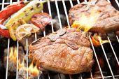 foto of flame-grilled  - Grilled pork chop and vegetables on the flaming grill - JPG