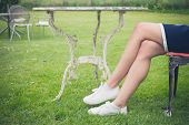 pic of lawn chair  - A young woman is sitting and relaxing on a chair on a lawn in a garden - JPG