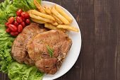 picture of pork chop  - grilled pork chop steak and vegetables with french fries on wooden background - JPG