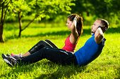 stock photo of abdominal muscle  - Man and woman exercising at the city park - JPG