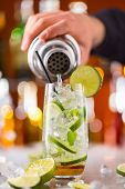 picture of mojito  - Mojito cocktail drink on bar counter with barman holding shaker - JPG