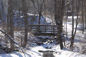 foto of ravines  - Little wooden bridge over rocky ravine surrounded by snow in a wooded area - JPG