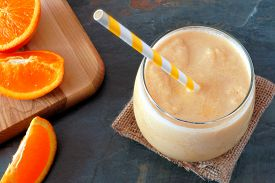 stock photo of orange  - Healthy orange smoothie in a glass with striped straw and fresh fruit slices downward view on slate - JPG