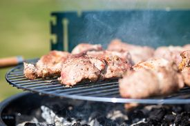 stock photo of grils  - Pork Meat Chop On The Barbeque Gril Outdoors - JPG