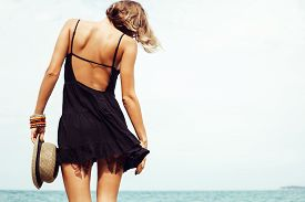 pic of rocking  - Outdoor summer sunny fashion portrait of pretty young sensual woman posing in black dress on the rocks on the ocean seashore - JPG