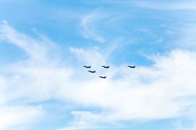 image of fighter plane  - flight of military fighter planes in white clouds in blue sky - JPG