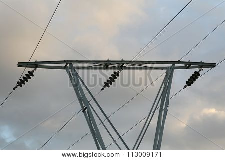 Silhouette Of Electricity Pylons Against An Evening Sky