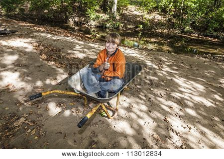 Child Sits In The Wheel Barrow And Relaxes