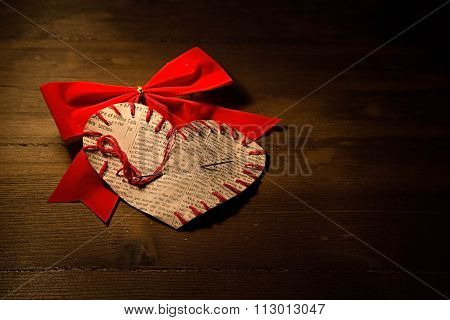 The Self-made Heart Sewed From A Newspaper Slice On A Red Bow, On Dark Wooden Boards