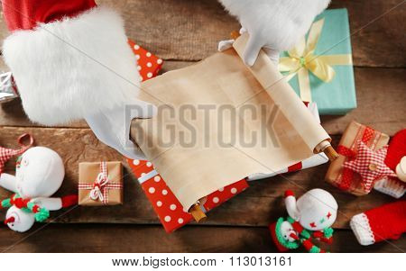 A list of Christmas wishes in Santa Claus hands, gifts and toys on wooden background