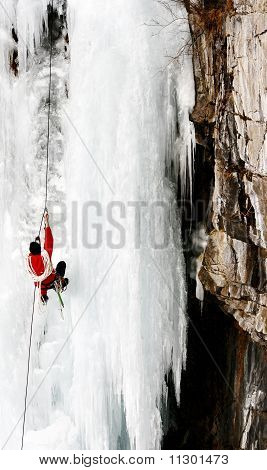 Alpinist climbing on the top of frozen waterfall