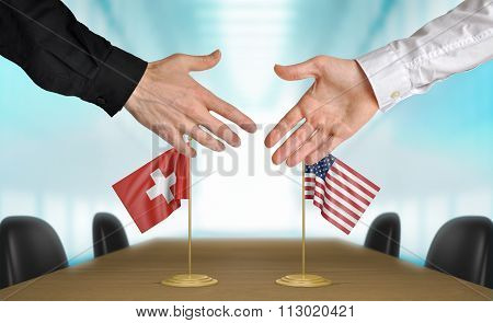 Switzerland and United States diplomats shaking hands to agree deal